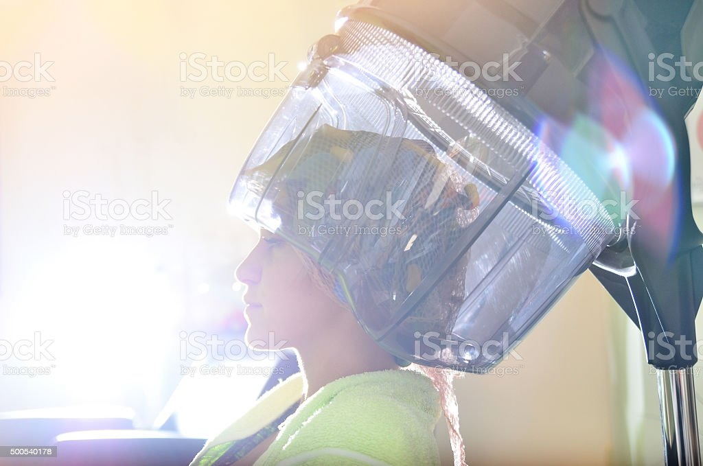 Woman at hair dresser, drying her curly hair under hood stock photo