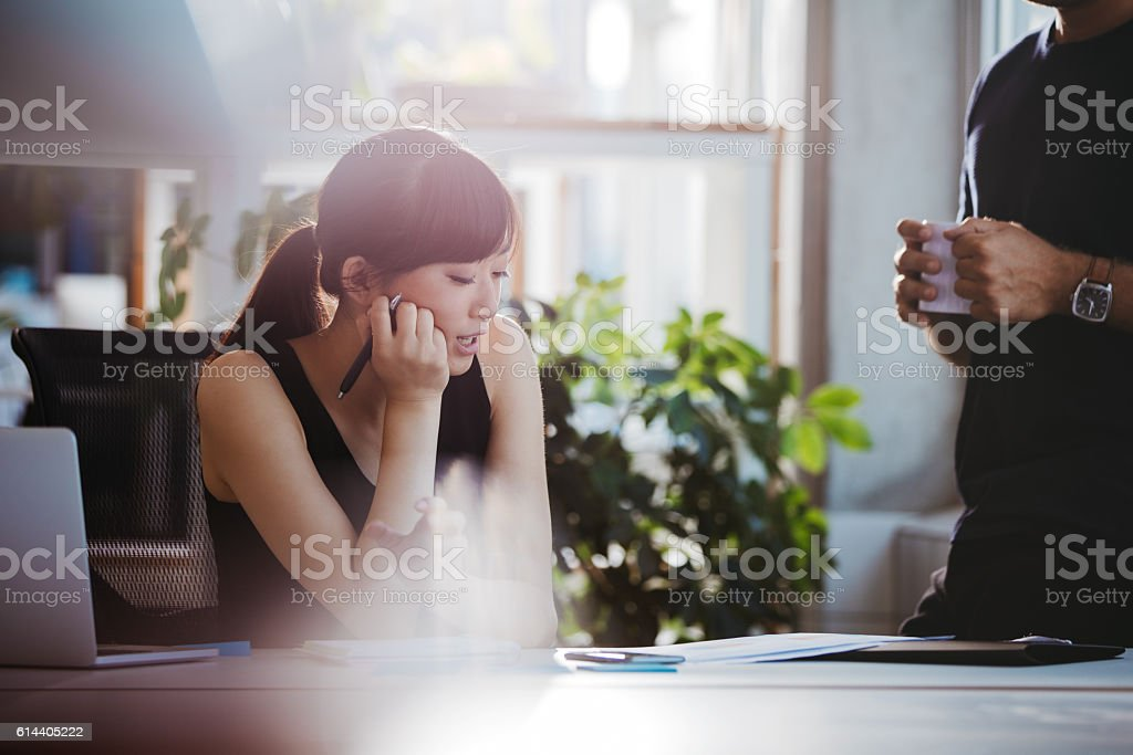 Woman at her desk and talking with male colleague stock photo