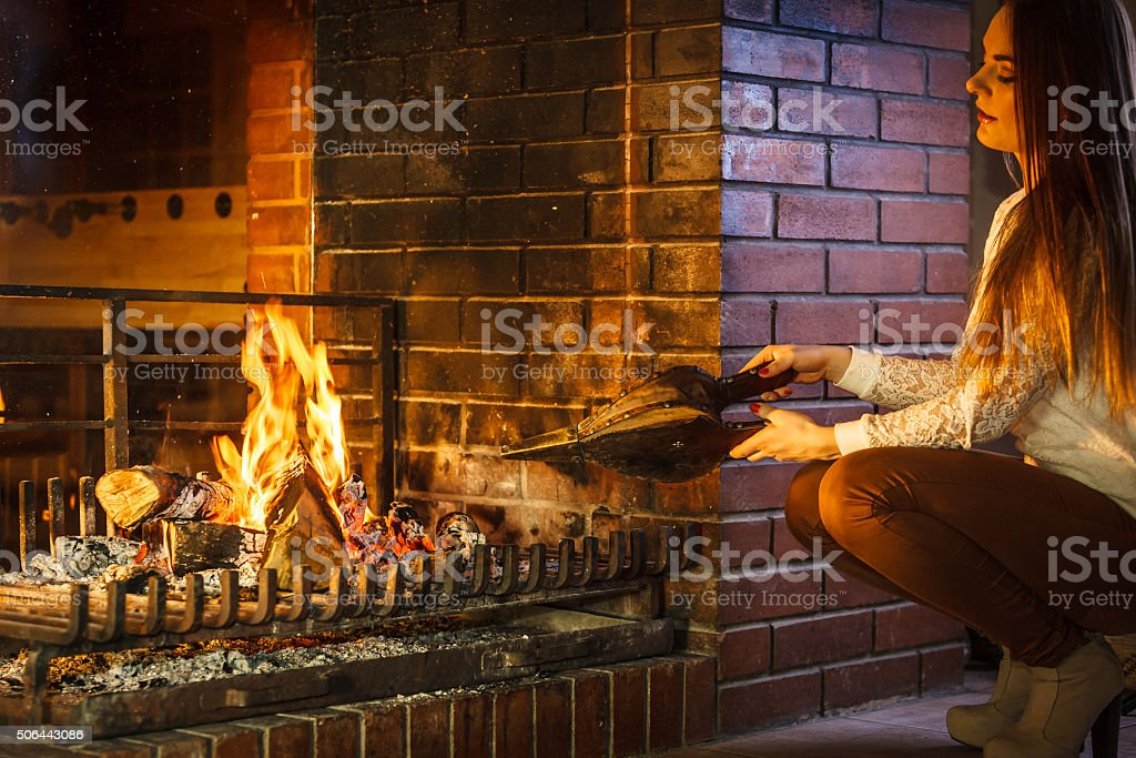 Woman at home fireplace making fire with bellows. stock photo
