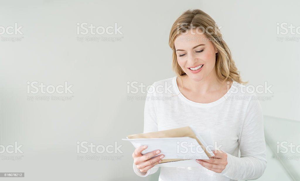 Woman at home getting the mail stock photo