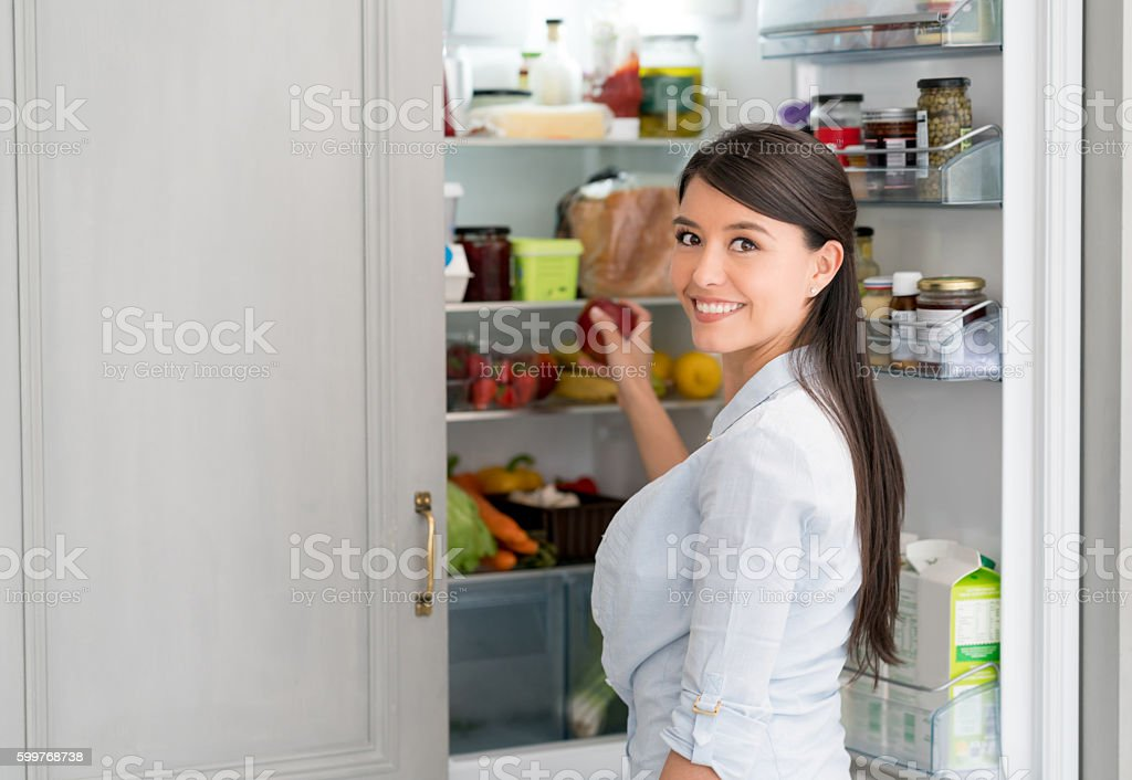 Woman at home opening the fridge stock photo