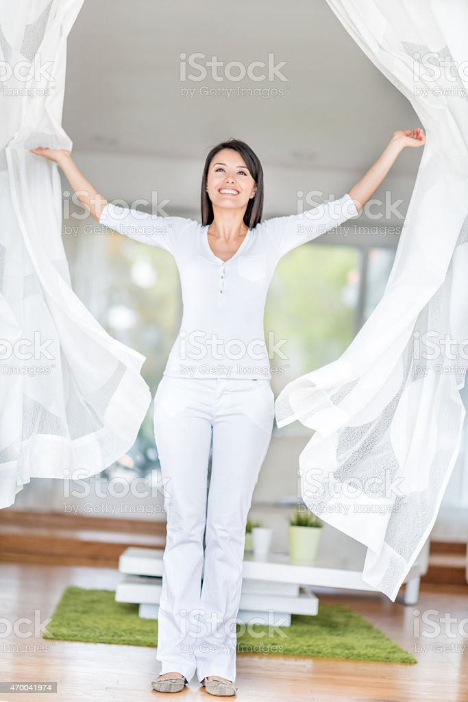 Woman at home opening the windows stock photo