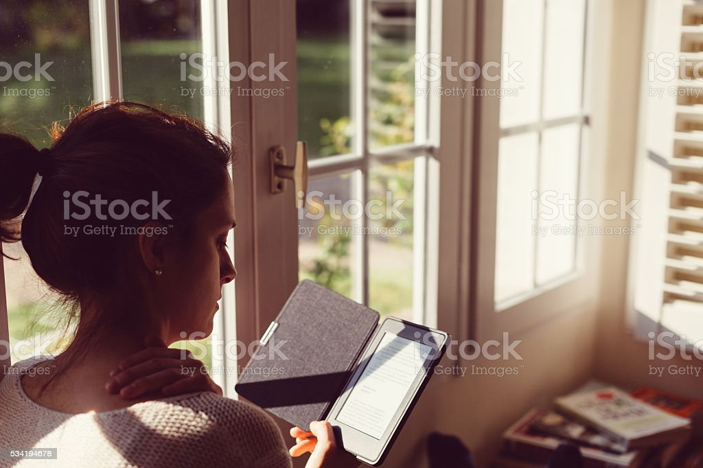 Woman at home reading e-book stock photo