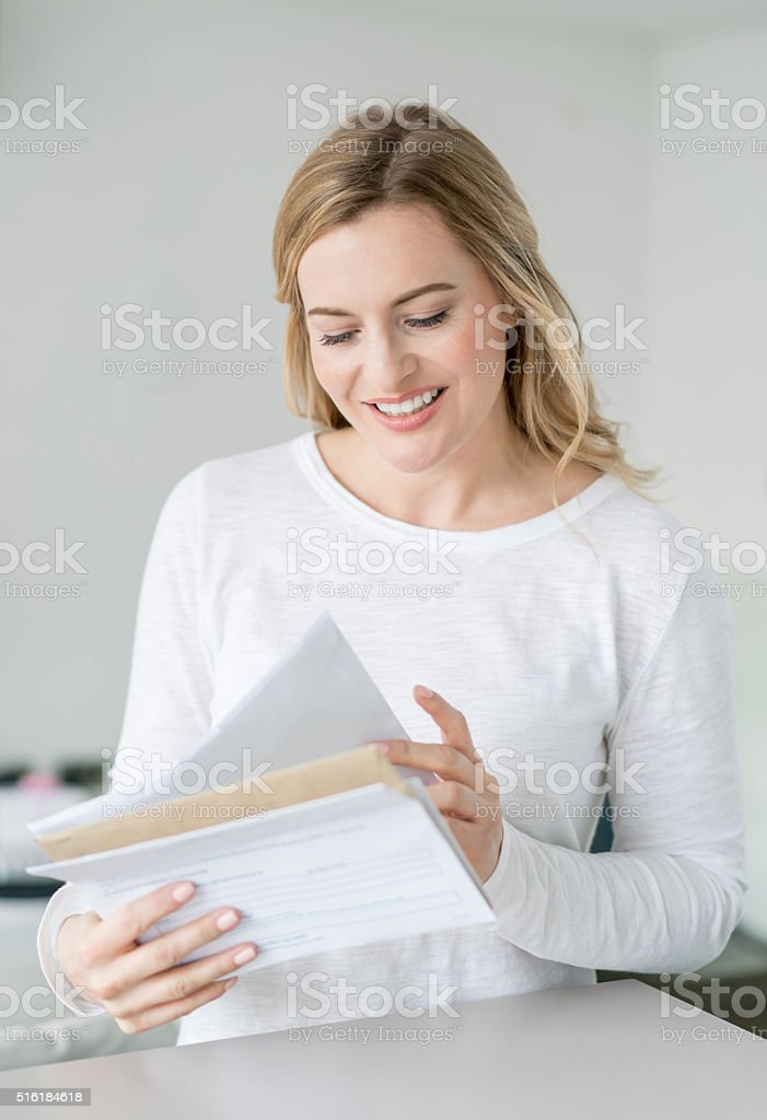 Woman at home reading the mail stock photo