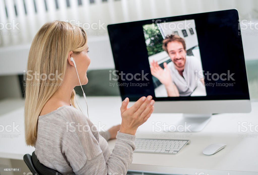 Woman at home video chatting with her boyfriend stock photo