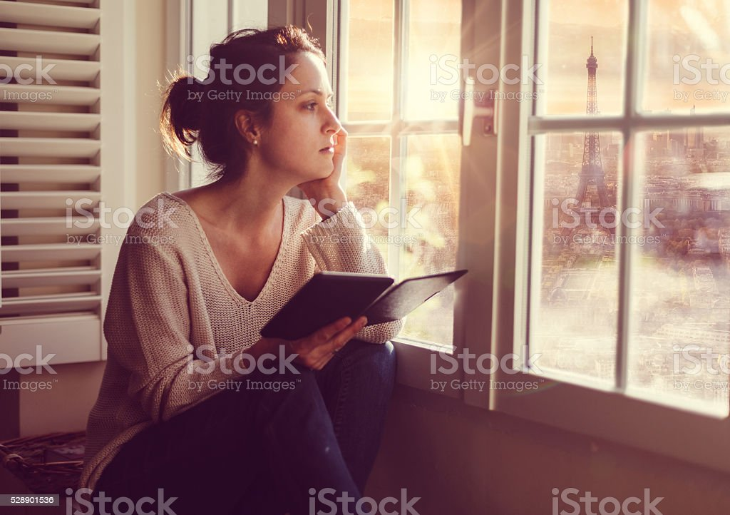 Woman at home watching Paris cityscape through the window stock photo