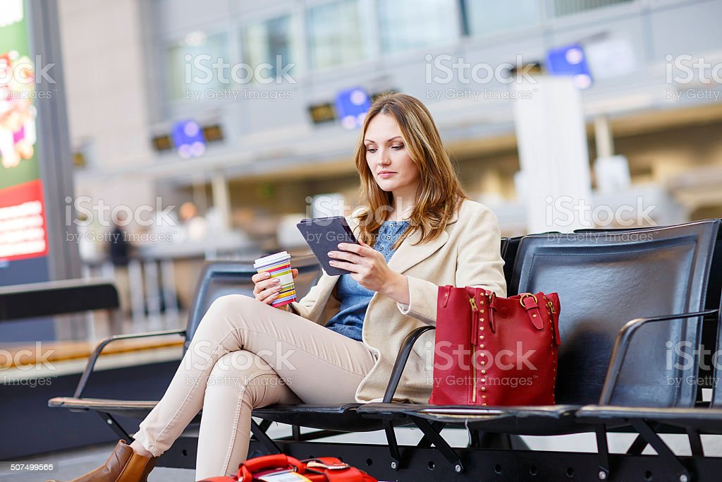 woman at international airport, reading ebook and drinking coffe stock photo