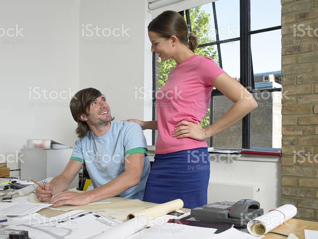 Woman at mans desk stock photo