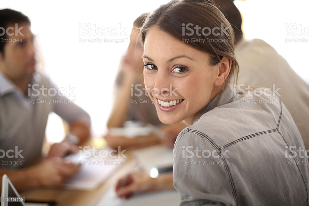 Woman at meeting looking back and smiling over her shoulder stock photo