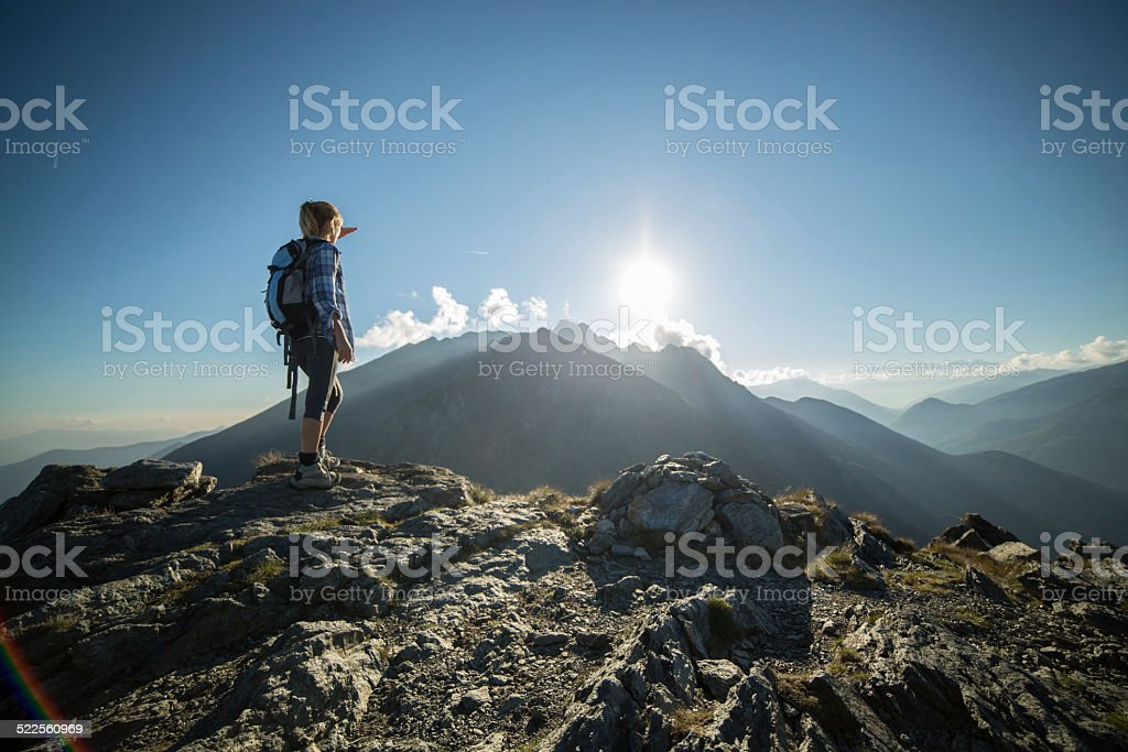 Woman at mountain peak looking at view stock photo