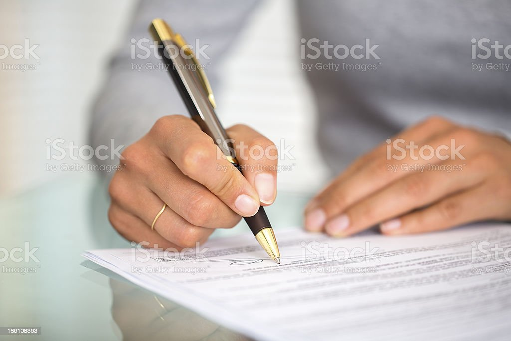 Woman at office desk signing a contract stock photo