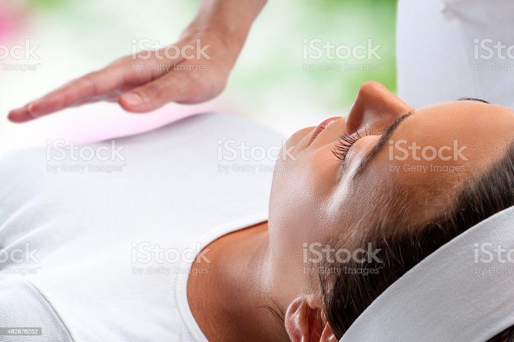 Femme de séance de reiki avec thérapeute main en arrière-plan. photo libre de droits
