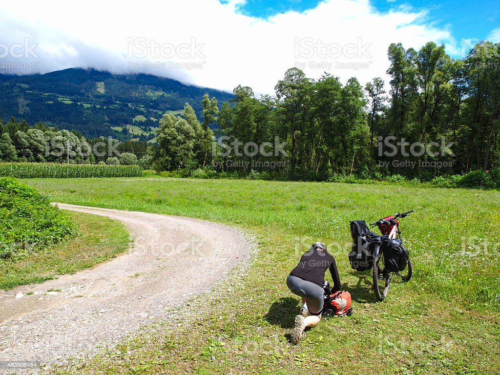Woman at rest at Drau cycle path in Austria stock photo