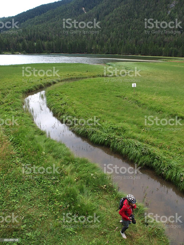 Woman at River Rienza flouting into Toblach Lake stock photo