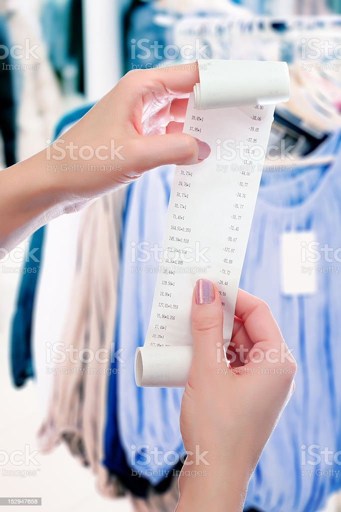 woman at shop holds roll of paper with printed receipt royalty-free stock photo