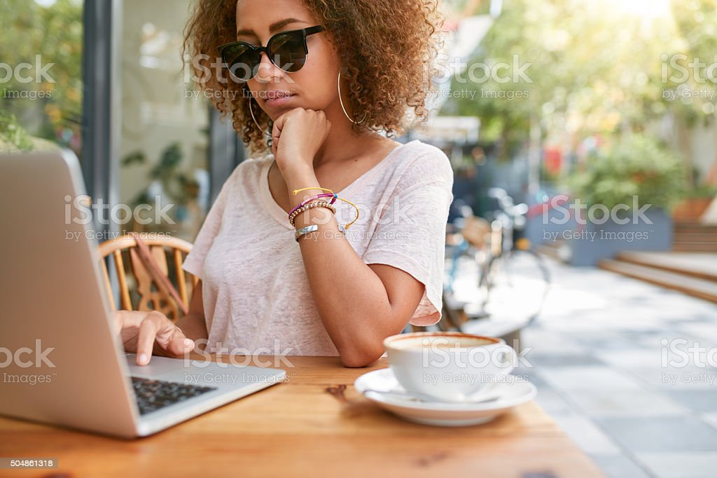 Woman at sidewalk cafe reading emails stock photo