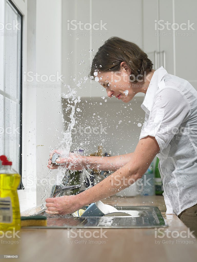 Woman at sink in domestic kitchen being drenched by broken tap, side view stock photo