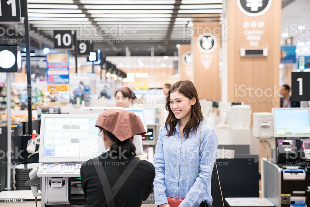 Woman at supermarket check out cash register ready to pay stock photo