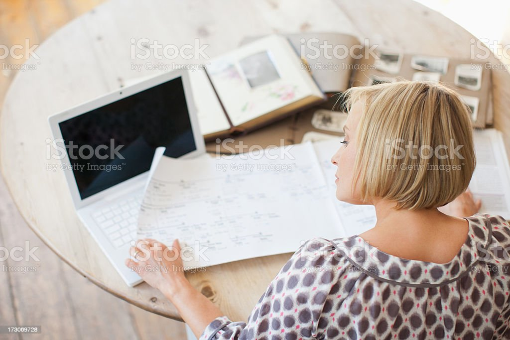 Woman at table looking at genealogical tree stock photo
