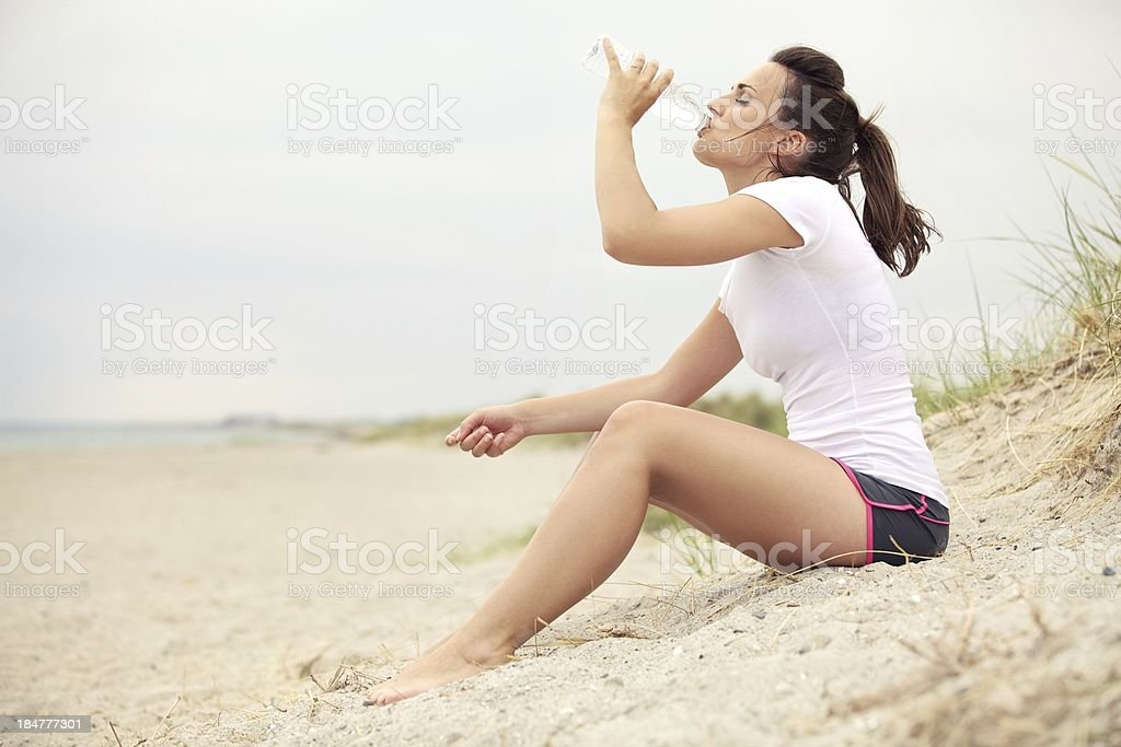 Woman at the Beach Drinking Water royalty-free stock photo