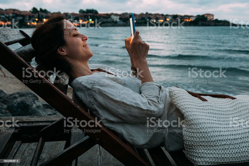 Woman at the beach texting stock photo