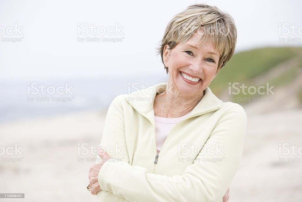 Woman at the beach with arms crossed smiling stock photo