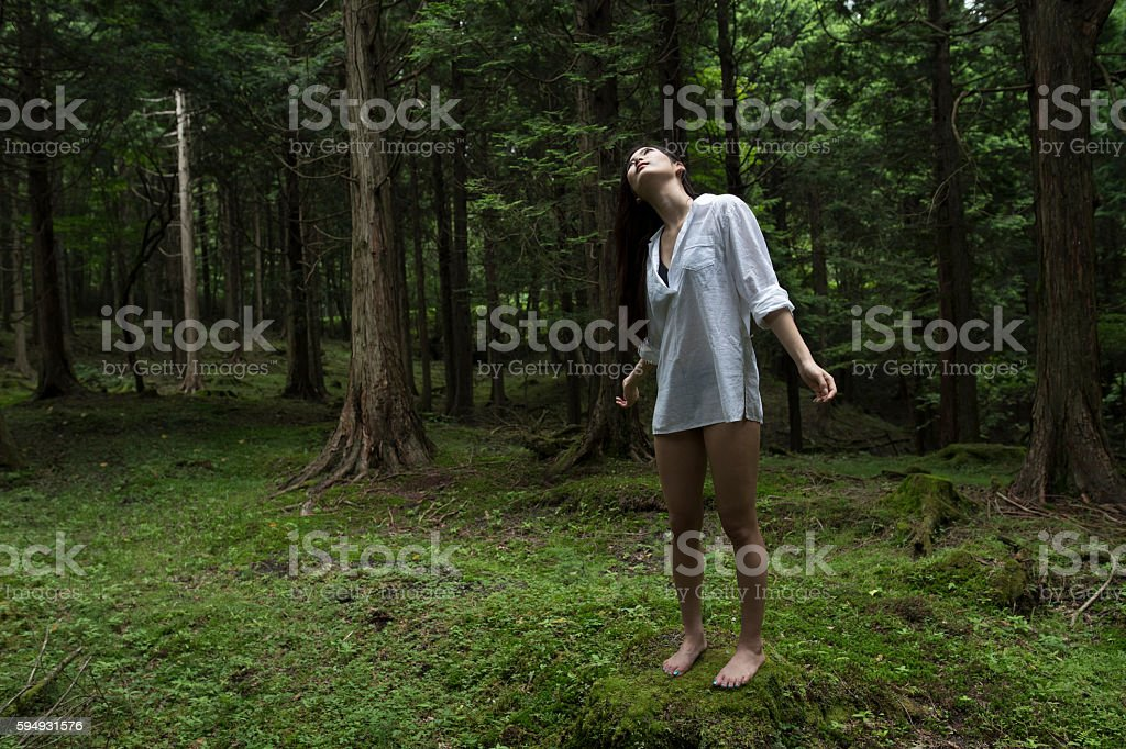 Woman at the center of the sacred forest. stock photo