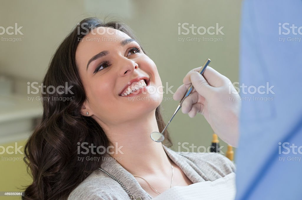 A woman at the dentist getting her teeth checked out stock photo