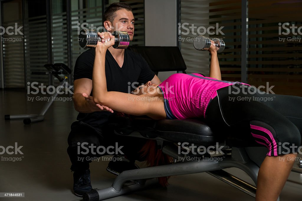 Woman at the gym with personal trainer royalty-free stock photo