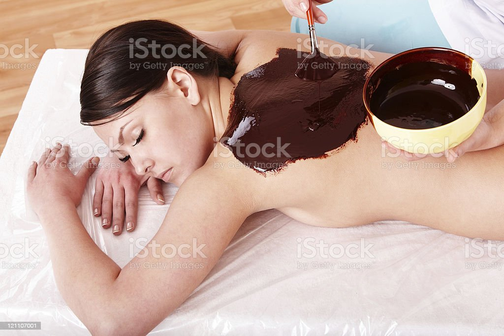 Woman at the spa getting treated with a chocolate body mask stock photo