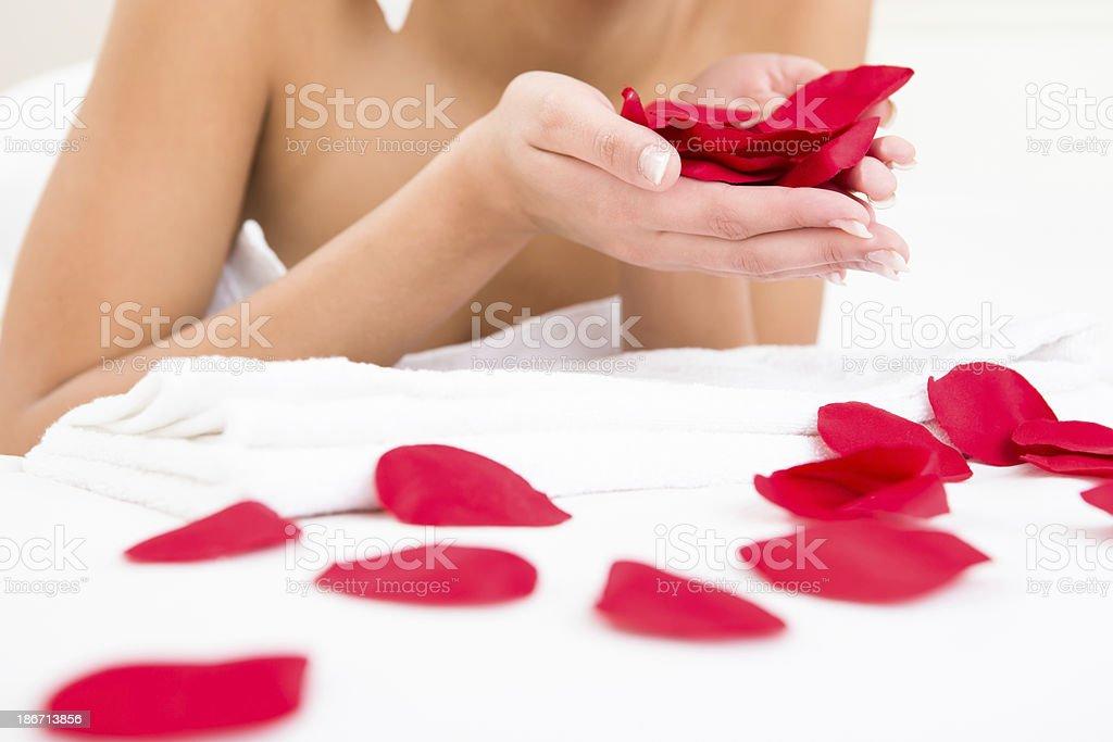 Woman at the spa holding rose petals royalty-free stock photo