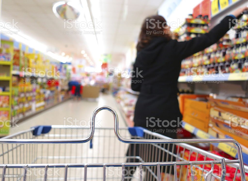 Woman at the supermarket with trolley royalty-free stock photo