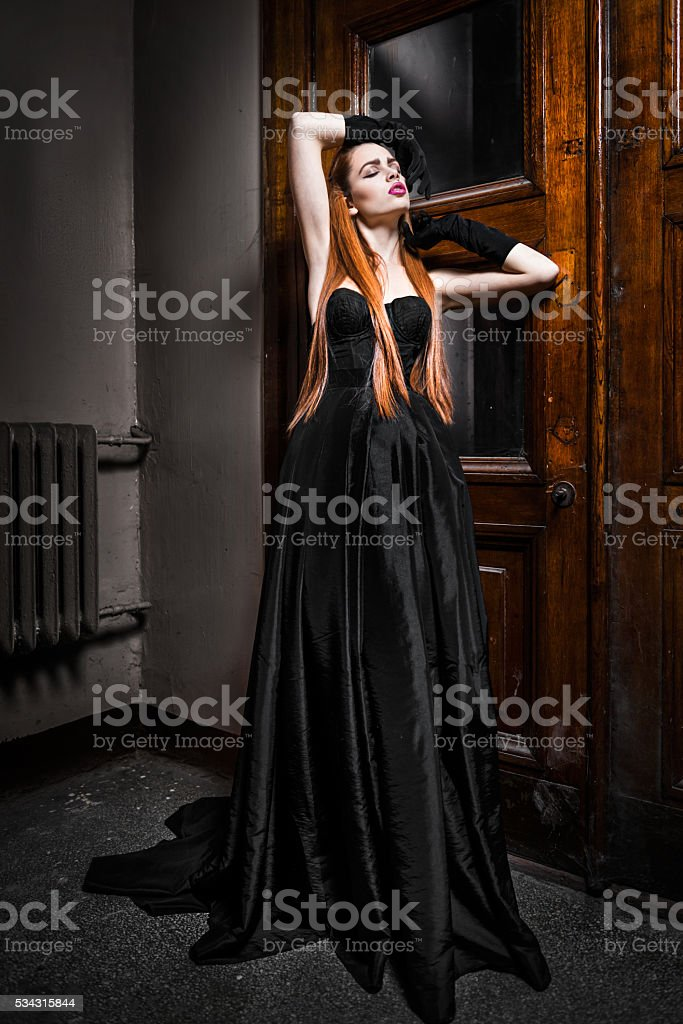 Woman at the wooden door in gothic styled dress stock photo