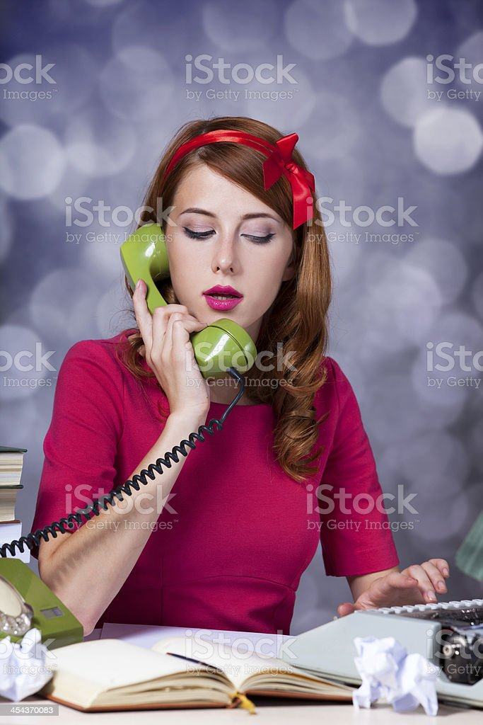 Woman at typewriter on telephone royalty-free stock photo