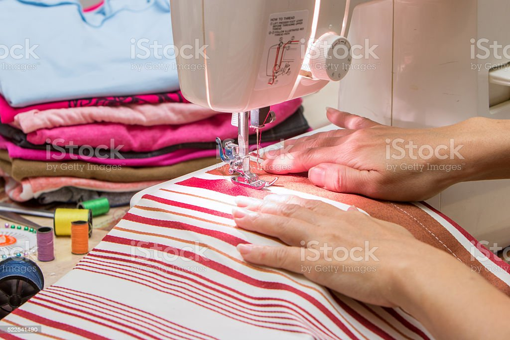 woman at work on sewing machine stock photo