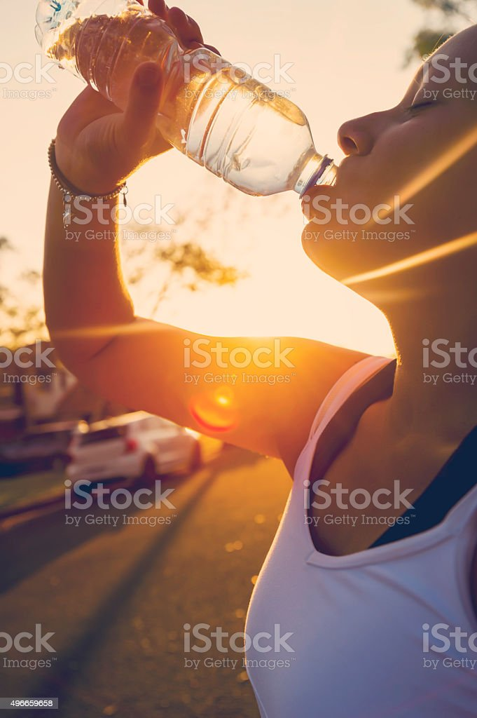 Woman athlete drinking water from a bottle stock photo