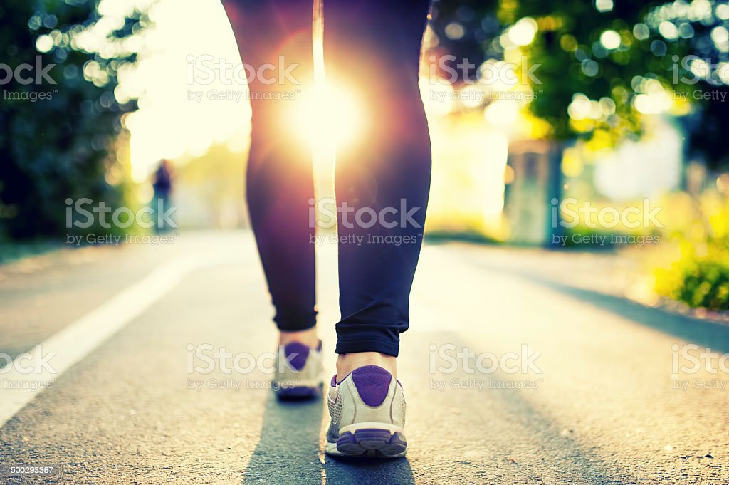 woman athlete feet and shoes while running in park. stock photo