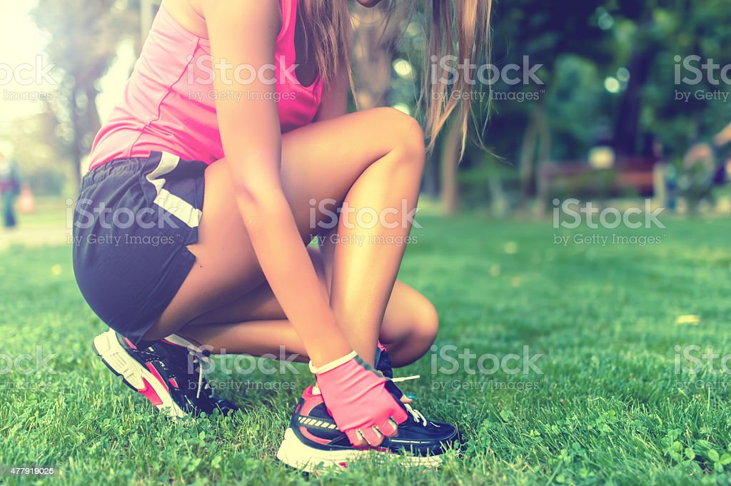 woman athlete feet, shoes and laces while running in park stock photo