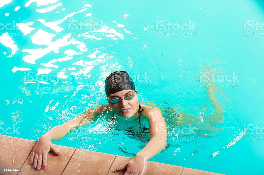 Woman athlete in swimming pool water. Water sport comptetition...