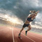 Woman Athlete Sprinting From Blocks on Running Track in Stadium