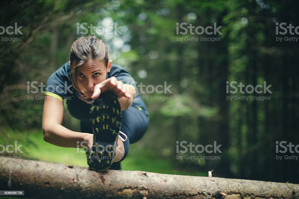 Woman athlete stretching in the forest after running stock photo