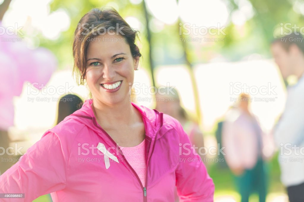 Woman attending 5k charity race for breast cancer research stock photo
