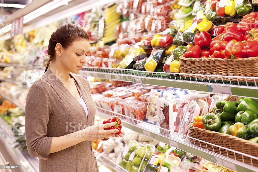 Woman attentively contemplating vegetable purchase at market stock photo