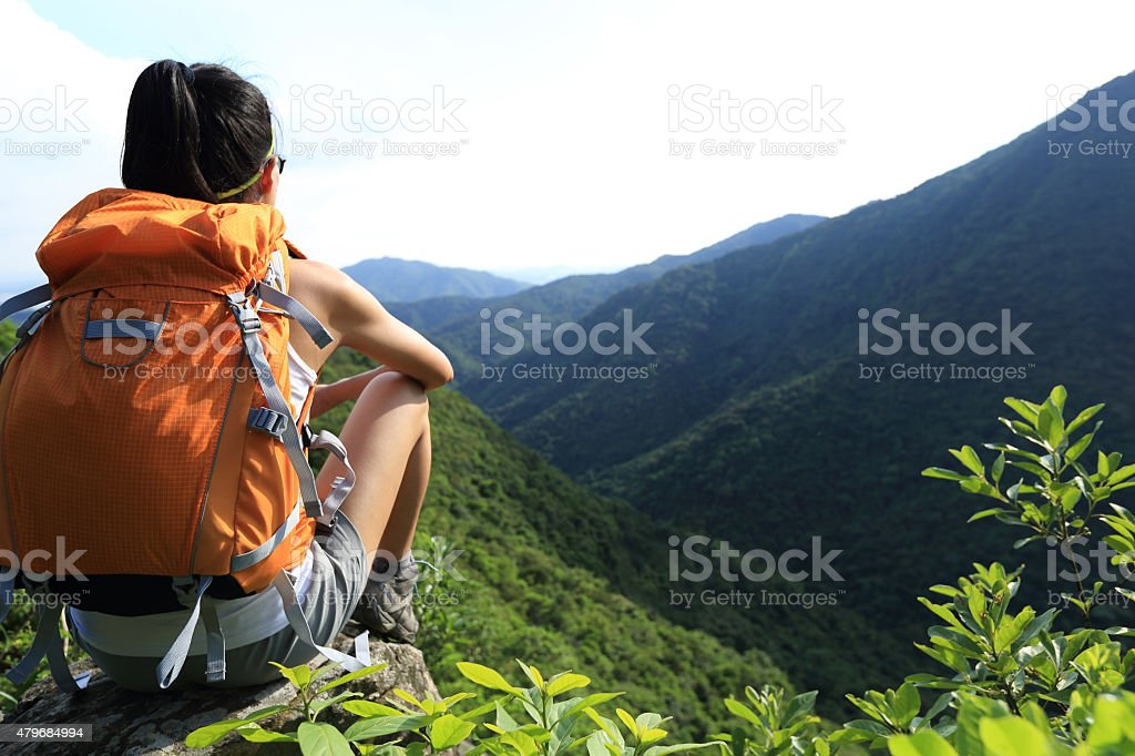 woman backpacker enjoy the view at mountain peak cliff stock photo