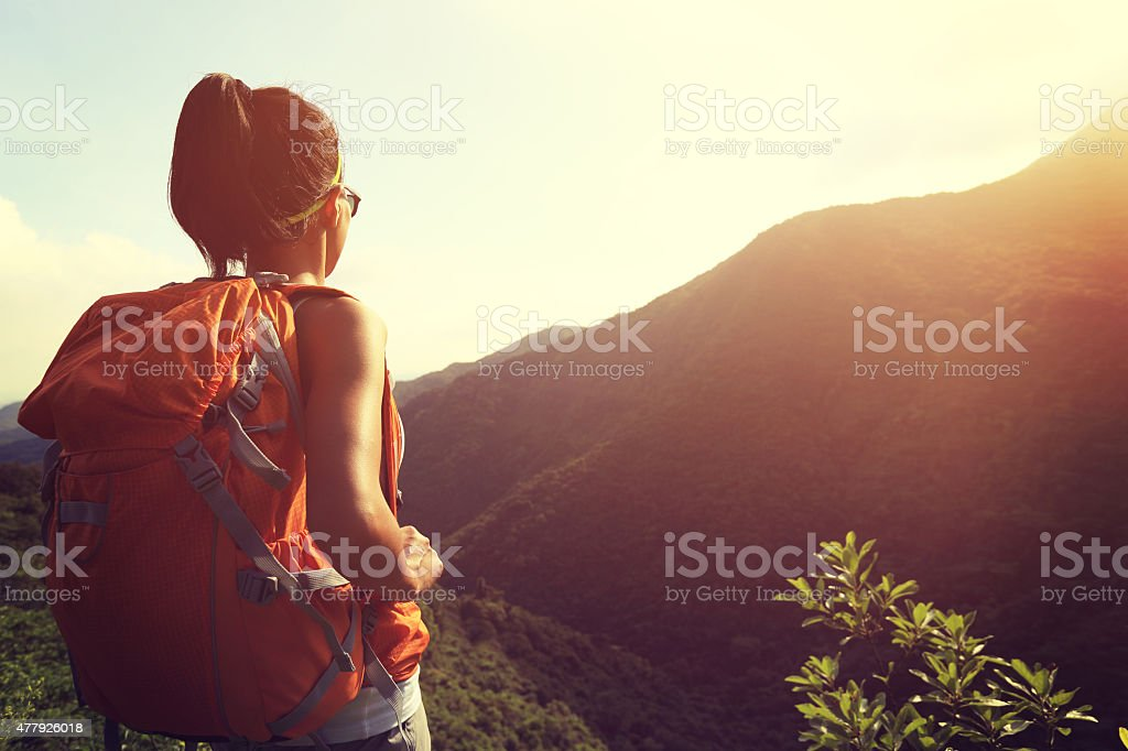 woman backpacker enjoy the view at mountain peak stock photo