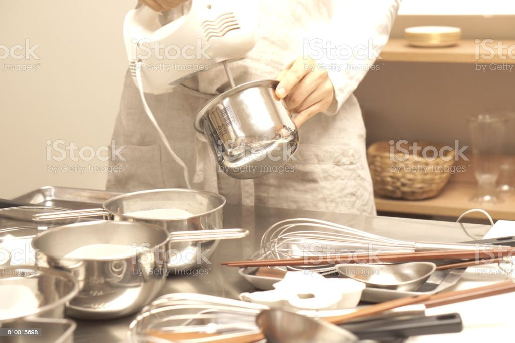 Woman baking, using electric hand mixer in kitchen stock photo