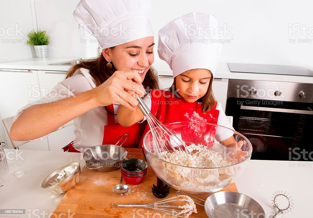 woman baking with little daughter in cook hat at kitchen stock photo