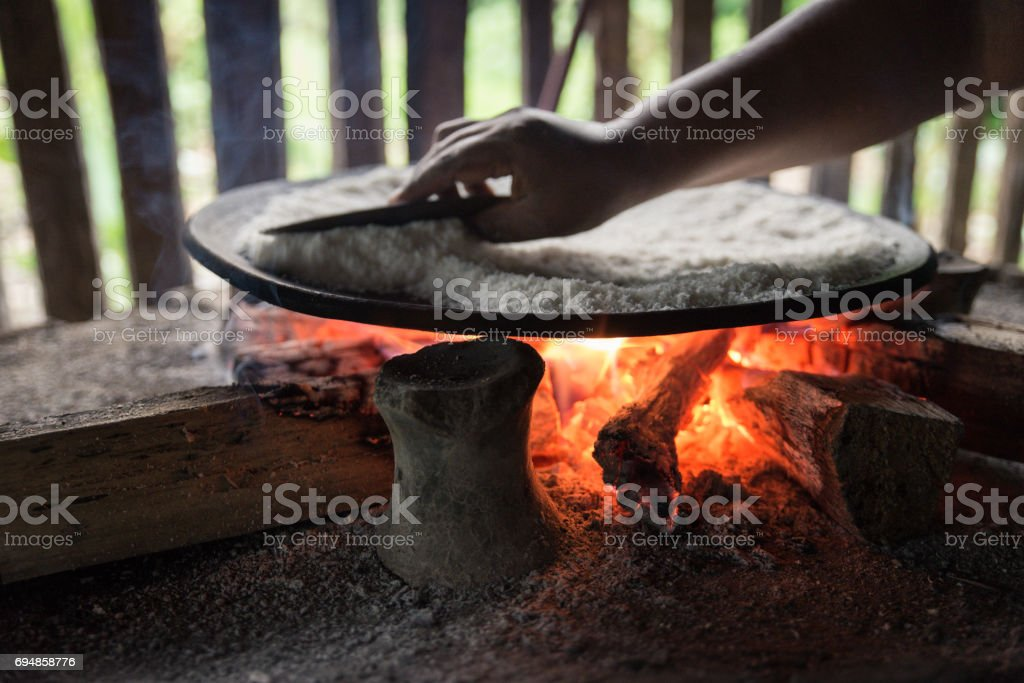 woman baking yuca bread over the fire stock photo
