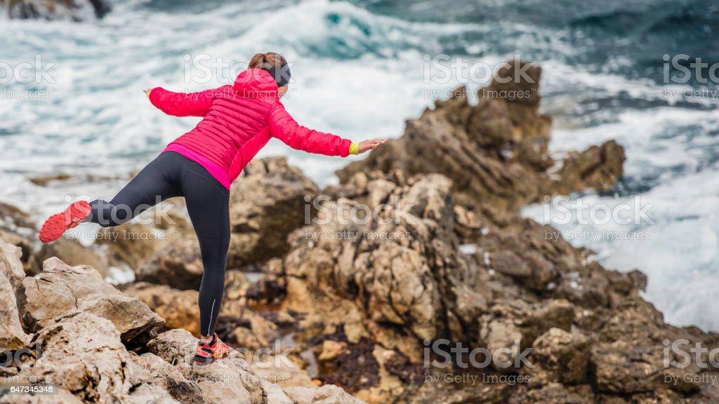 Woman balancing on rock stock photo