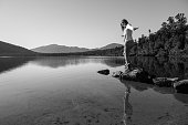 Woman balancing on stepping stones by the lake, BW